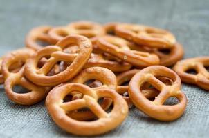 Heap of fresh Wheat salt pretzels on hessian linen fabric photo