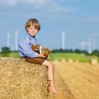 Funny little kid boy sitting on hay stack  eating pretzel photo