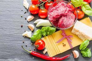 ingredientes de lasaña: láminas secas, carne, tomates cherry, queso, cebolla foto