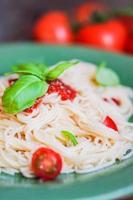 espagueti con tomate y albahaca sobre fondo de madera foto