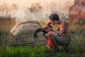 Man cleaning Thai gamecock