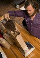 hombre de embalaje de café vierte frijoles en bolsa foto