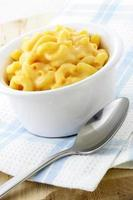 Macaroni cheese in a white dish next to a silver spoon