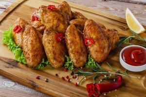 alitas de pollo fritas con salsa roja foto