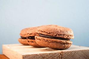 Chocolate flavor Macaroon placed on wood and leather