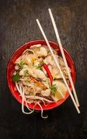 Asian noodles with chopstick, chicken and sprouts on wooden background