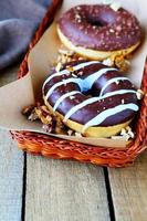 two chocolate donuts with nuts