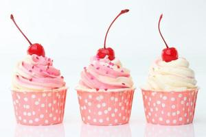 Cupcake with whipped cream and cherry isolated on white