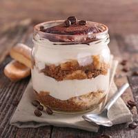 Creamy delicious tiramisu served in a mason jar on a table