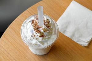 Frappe de chocolate helado y crema batida en una taza para llevar