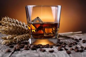 Glass of whiskey with coffee beans and wheat.