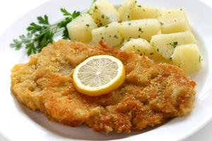 Breaded veal cutlet served with potatoes and lemon slice photo