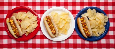 varios perritos calientes en platos de colores foto