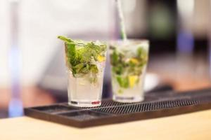 Two Mojito cocktails on a bar counter