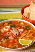 Chicken tortilla soup with lime and chips photo