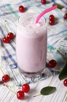 milkshake with cherry juice in a glass. vertical top view photo