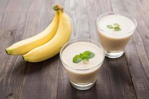 Banana smoothie on wooden table. photo