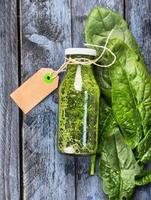 Batido de espinacas verdes en botella con signo sobre fondo de madera foto