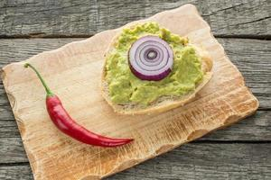 Roll spread with avocado, chili pepper and onions