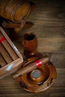 cigarros con barril de ron en la mesa foto