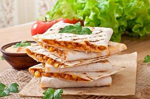Mexican Quesadilla sliced with vegetables and sauces