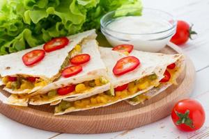 Mexican quesadilla slices served on wood board with yogurt sauce