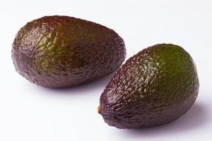 two avocados on white background