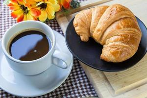 Some croissants, bread and coffeeon dish