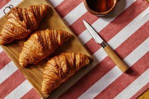 Three french freshly baked croissants on wooden plate with honey