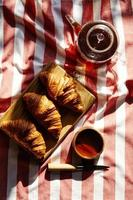 Three french freshly baked croissants on wooden plate with teapo