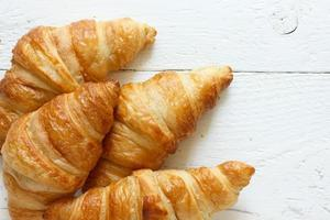 Golden croissants on rustic white wood, from above. photo