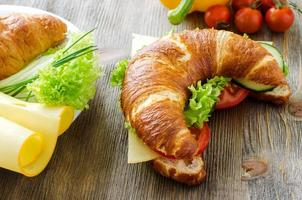 Croissant sandwich with cheese and vegetables for healthy snack, photo