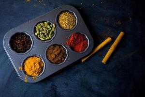 Closeup of various colorful spices bowl on table photo