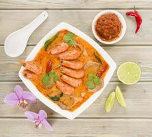 Overhead view of bowl of Tom Yum Nam Khon on a wooden table