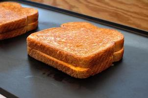 Two grilled cheese sandwiches on a hot plate photo