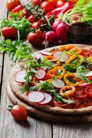 Vegan pizza with radish, tomato and paprika