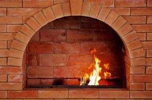 Brick oven in center of brick wall with fire lit