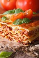 Tasty lasagna with basil and tomatoes on table, vertical photo