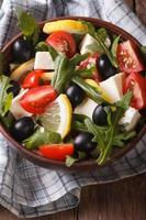 salad of arugula, feta, olives and tomatoes  vertical top view photo