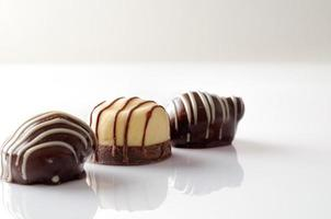 Three bonbons on a white table Front view Close up photo