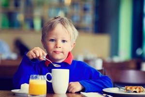 little boy eating breakfast in cafe
