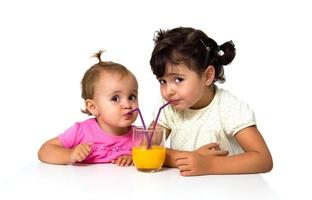 kleine meisjes die sinaasappelsap drinken