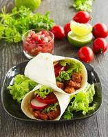 Burrito with pork and tomatoes.