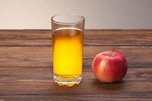 Glass of apple juice and red apple on wood photo