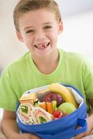 Young boy holding packed lunch