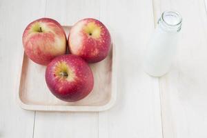 maçã e leite em garrafa em fundo de madeira