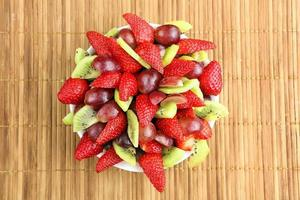Fruit salad with strawberries, grapes and kiwi on rattan backgro