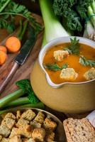 Fresh creamy carrot soup on rustic wooden table