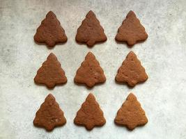 Gingerbread Christmas cookies shaped like trees on kitchen counter top