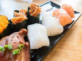 Squid sushi with variety of sushi on black dish